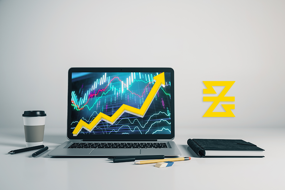 laptop display with forex trading platform and yellow trend line up next to baxia symbol
